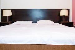 Säng med vit täcker och kudde med lampan för sängkant två på Royaltyfria Foton