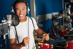 Sångare som antecknar hans nya spår i studio Arkivbilder