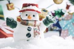 Snögubben och den ljusa kulan står bland högen av snö på den tysta natten, tänder upp hopefulnessen och lyckan i glad jul och slu Arkivfoto