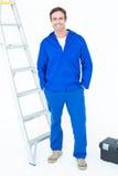 Snickare i overaller som står med händer i fack Arkivfoton