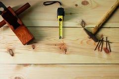 Snickare` s för snickeri Den gamla hammaren och spikar och tränivån och mätabandet på texturträbakgrund fotografering för bildbyråer