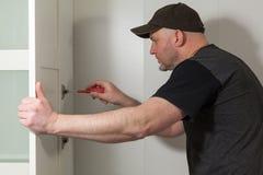 Snickare som arbetar på ny garderob Faktotum som fixar en dörr i en garderob royaltyfri foto