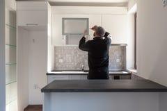 Snickare som arbetar på nytt kök Faktotum som fixar en dörr i ett kök arkivfoton
