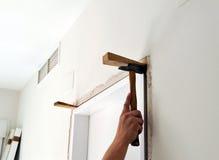 Snickare som förlägger en ny dörr i reformen av huset Royaltyfria Bilder