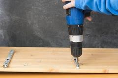 Snickare som förlägger skruvar med en drillborr Royaltyfri Foto