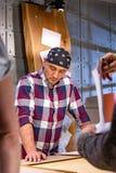 Snickare som gör hans jobb i snickeriseminarium en man i ett snickeriseminarium mäter och snittlaminat arkivbilder