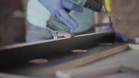 Snickare som gör korridorer i träflismaterialdetaljerna med sladdlös skruvmejsel Begrepp av handtillverkning Craftman arbetar arkivfilmer