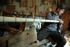 Snickare som handcrafting en träalpenhorn Arkivbilder