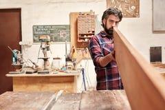 Snickare som kontrollerar expertly en träplanka för straightness och royaltyfri fotografi
