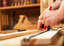 Snickare som markerar en mätning på en träplanka Royaltyfri Fotografi
