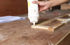 Snickare som sätter lim på ett stycke av trä arkivfoto