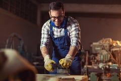 Snickare som sandpapprar och förbereder trä på tabellen i tygseminariet royaltyfri fotografi