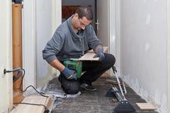 Snickare som sandpapprar och klipper nya golvbräden Royaltyfria Bilder
