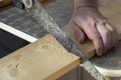 Snickarehand med den gamla handsawen som klipper träbräden arkivbilder
