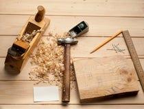 Snickarehjälpmedel, hammaren, meter, spikar, shavings, och Royaltyfria Bilder