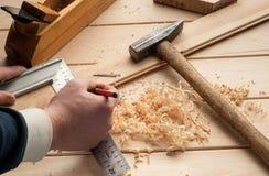 Snickarehjälpmedel, hammaren, meter, spikar, shavings, och Arkivfoton