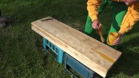 Snickaremannen räcker att måla träplankabrädet med borsten på gräs closeup 4K stock video