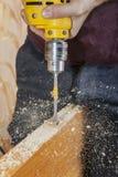 Snickaren borrar låser hålet av dörrlåset, genom att använda spadebiten Arkivbild
