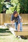 Snickaren Cutting Wood With såg på konstruktion royaltyfri fotografi