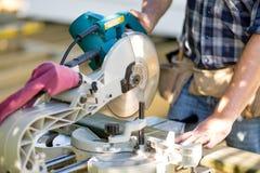 Snickaren Cutting Wooden Plank med tabellen såg på royaltyfri foto