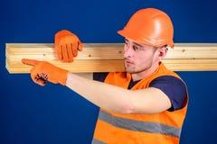 Snickaren inredningssnickare, den starka byggmästaren på upptagen framsida bär trästrålen på skuldra Man i hjälmen, hård hatt och Royaltyfri Fotografi