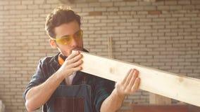 Snickaren kontrollerar kvaliteten som sandpapprar träbrädet arkivfilmer