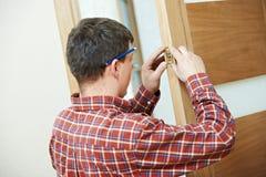 Snickaren på dörren låser installation royaltyfri bild