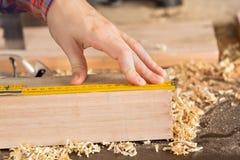 Snickares hand som mäter trä med skalan Arkivbild