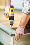 Snickares händer genom att använda drillborren på trä Arkivfoto