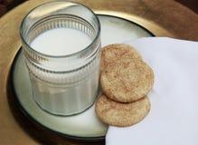 Snickerdoodle kakor på den guld- plattan med exponeringsglas av mjölkar arkivbild