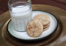 Snickerdoodle kakor på den guld- plattan med mjölkar arkivfoton