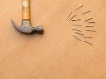 Snickeri hammare och spikar på träbräde Arkivbild