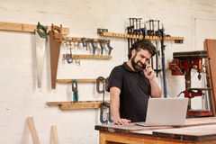 Snickerismå och medelstora företagägare på hans telefon med en bärbar dator arkivfoto
