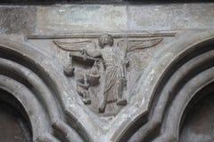 Snida av demonen och ängeln med våg i kyrka Arkivfoton
