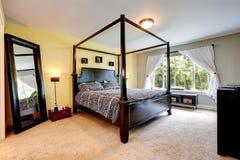Sniden wood säng med höga poler framförd inre blixt för omgivande sovrum 3d Fotografering för Bildbyråer