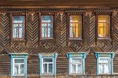 Snidit fönster i trälandshus för gammal ryss Arkivfoto