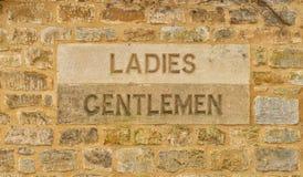 Snidit i stenmina damer och herrar underteckna i Cotswoldsen royaltyfri fotografi