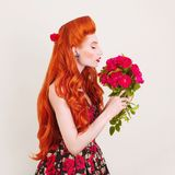 Sniff flower. Valentines day concept. Beautiful bouquet of flowers. Enchanting redhead model with hairstyle sniff bouquet of roses. Isolated on gray background stock photo