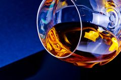 Snifter of brandy in elegant glass with space for text on light tint blue disco Stock Images