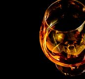 Snifter of brandy in elegant typical cognac glass on black background Royalty Free Stock Images