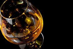 Snifter of brandy in elegant typical cognac glass on black background Stock Photo
