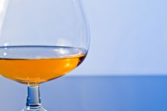 Snifter of brandy in elegant typical cognac glass on blue light background Stock Photos