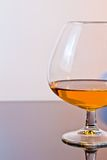 Snifter of brandy in elegant typical cognac glass on light background Royalty Free Stock Images