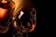 Snifter of brandy in elegant typical cognac glass near near bottle on black table Royalty Free Stock Photos