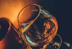 Snifter of brandy in elegant typical cognac glass near near bottle on black table, warm tint style Royalty Free Stock Image