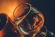 Snifter of brandy in elegant typical cognac glass near near bottle on black table, warm tint style. Snifter of brandy in elegant typical cognac glass near bottle Royalty Free Stock Image