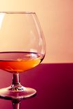 Snifter of brandy in elegant typical cognac glass on purple colored light disco background Royalty Free Stock Images