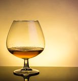 Snifter of brandy in elegant typical cognac glass on table with reflection Stock Photos