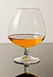 Snifter of brandy in elegant typical cognac glass on white light background Royalty Free Stock Photography