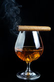 Snifter glass of cognac and cigar Royalty Free Stock Images